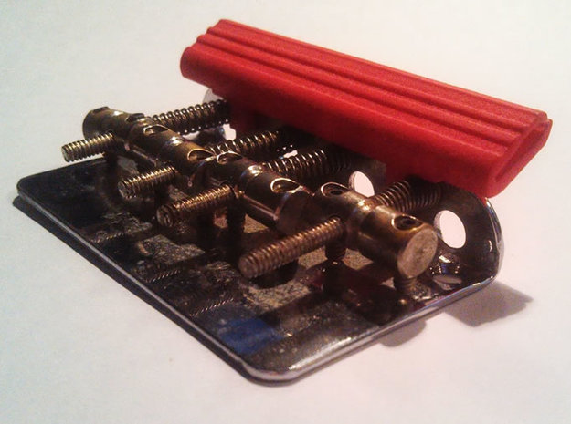 "Bridge Pick Holder - Stock Fender - Lines 3d printed BPH ""Lined"" design in Polished Red on a stock Fender bass bridge."