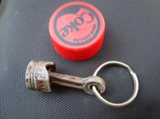 """Piston Keychain 4cm 3d printed Printed in white detail, painted for """"used"""" look, with a 0,5L coke bottle cap for scale."""