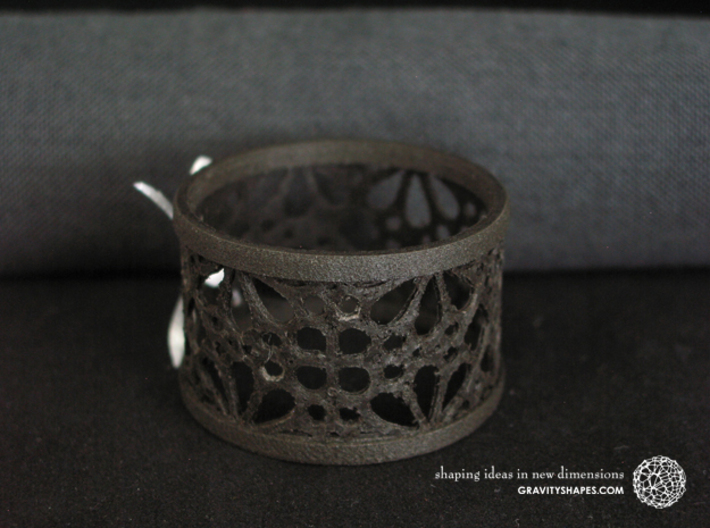 A large napkin ring with Mosaic-3a 3d printed The photo shows an own print (FDM print) made of black wood incl. decorative lacing.
