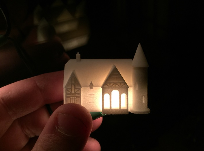 Alton Haunted house 3d printed In white with a fairy light inside showing the detail, it also shows the scale of the model