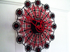 Kaleidoscope Clock - Part A 3d printed The completed Kaleidoscope Clock with Part A in Black Strong & Flexible and Part B in Red Strong & Flexible.This is a two-part clock face kit. This model is Part A. The second part is available at http://www.shapeways.com/model/580493